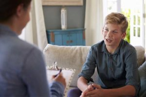 young boy talking to addiction specialist during the adolescent rehab center program in oh